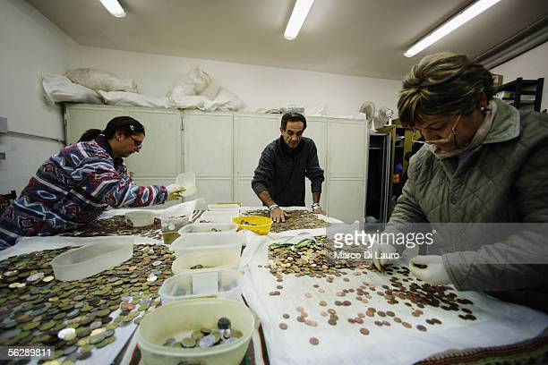 Francesco an AIDS patient and two Caritas employees process coins collected from the Trevi Fountain November 28 2005 in Rome Italy Tourists from all...