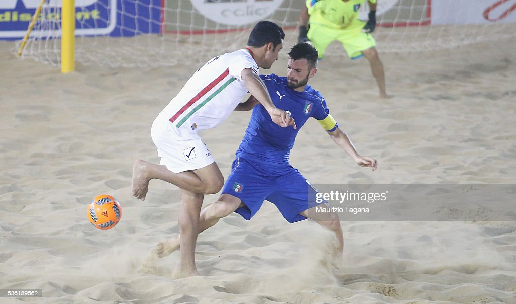 Francesco Carosiniti of Italy competes for the ball with Mesigar of Iran during the beach soccer international frienldy between Italy and Iran on May 31, 2016 in Catania, Italy.