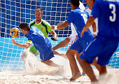 Francesco Corosiniti of Italy heads the ball towards the goal as goalkeeper David Ficsor of Hungary defends in the Men's Beach Soccer first round...