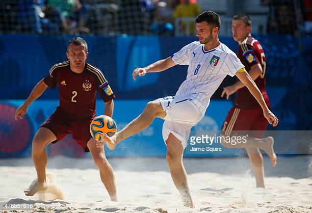Francesco Corosiniti of Italy is watched by Ilia Vlasov of Russia the Men's Beach Soccer gold medal match between Italy and Russia on day sixteen of...
