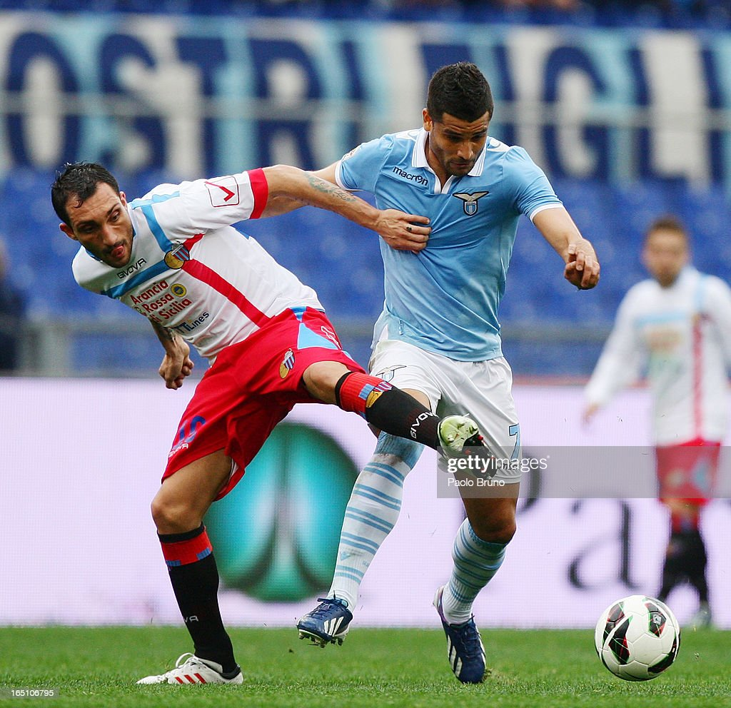 Francesco Lodi of Calcio Catania competes for the ball with Honorato Ederson (R) of S.S. Lazio during the Serie A match between S.S. Lazio and Calcio Catania at Stadio Olimpico on March 30, 2013 in Rome, Italy.