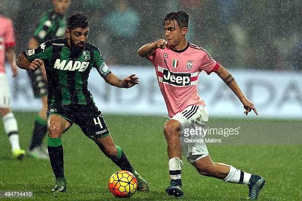 Francesco Magnanelli of US Sassuolo Calcio battles for the ball with Paulo Dybala of Juventus FC during the Serie A match between US Sassuolo Calcio...