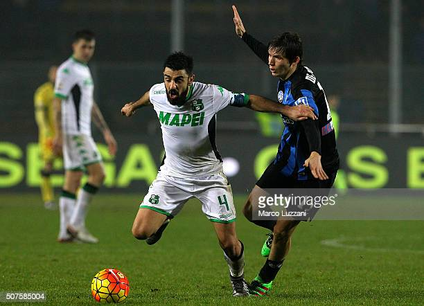 Francesco Magnanelli of US Sassuolo Calcio competes for the ball with Marten De Roon of Atalanta BC during the Serie A match between Atalanta BC and...