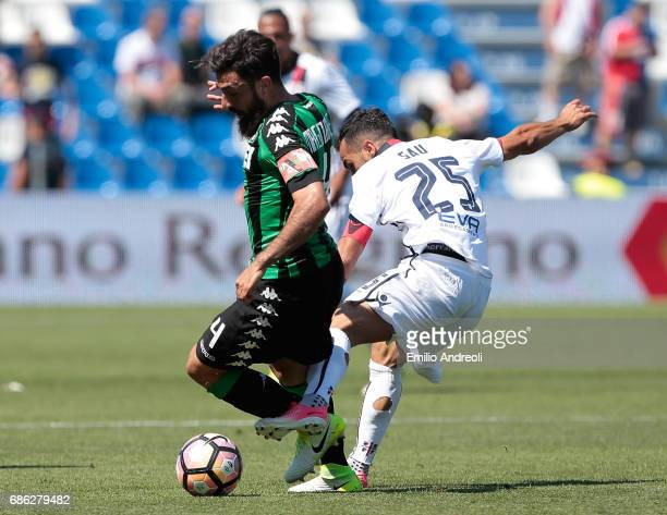 Francesco Magnanelli of US Sassuolo Calcio competes for the ball with Marco Sau of Cagliari Calcio during the Serie A match between US Sassuolo and...