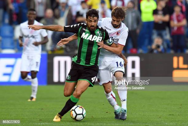 Francesco Magnanelli of US Sassuolo competes for the ball whit Andrea Poli of Bologna FC during the Serie A match between US Sassuolo and Bologna FC...
