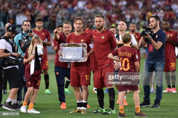 Francesco Totti holds a plaquet as he poses for a photo with Daniele De Rossi of AS Roma after the Serie A Week 38 match between AS Roma and Genoa...