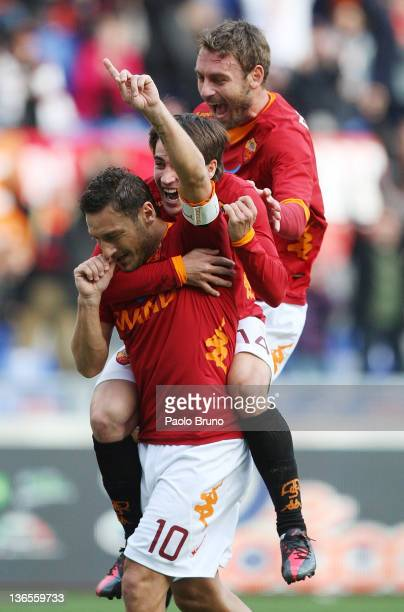 Francesco Totti of AS Roma celebrates with teammates Bojan Krkic and Daniele De Rossi after scoring a goal from the penalty spot during the Serie A...