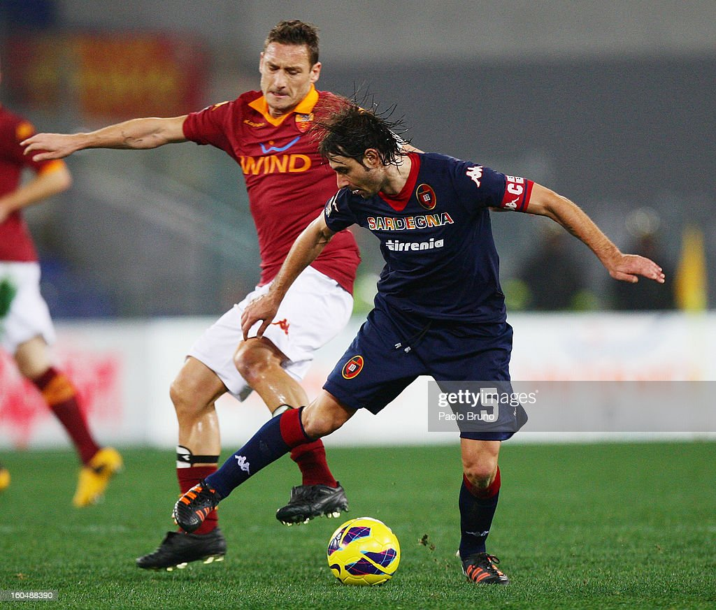 Francesco Totti (L) of AS Roma competes for the ball with Daniele Conti of Cagliari Calcio during the Serie A match between AS Roma and Cagliari Calcio at Stadio Olimpico on February 1, 2013 in Rome, Italy.