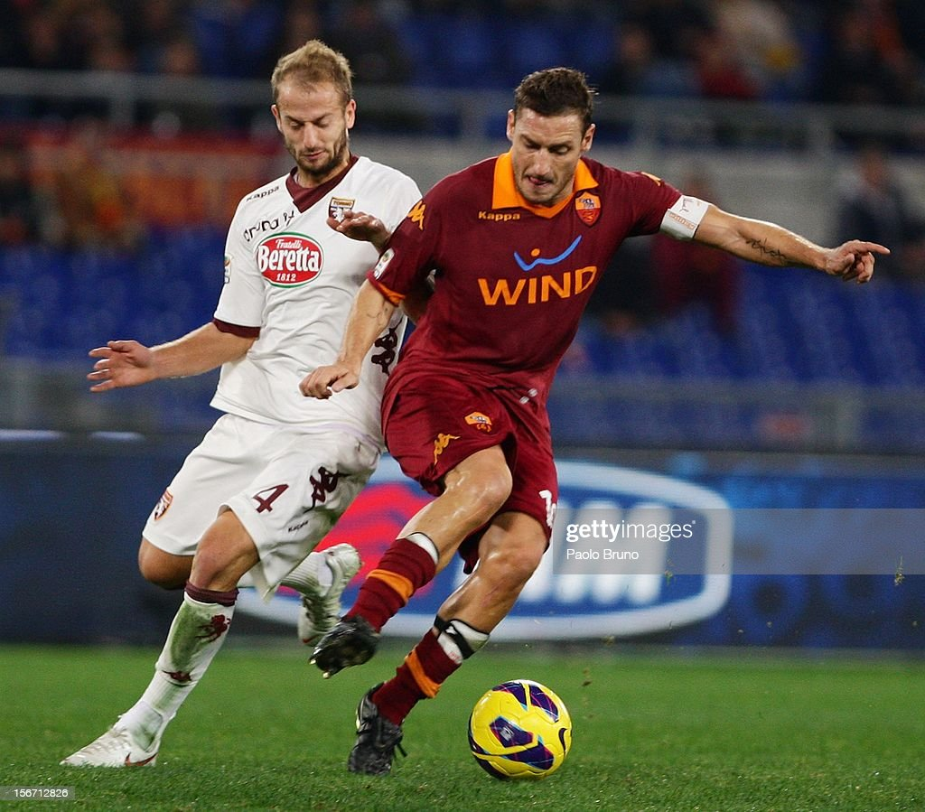 <a gi-track='captionPersonalityLinkClicked' href=/galleries/search?phrase=Francesco+Totti&family=editorial&specificpeople=208985 ng-click='$event.stopPropagation()'>Francesco Totti</a> (R) of AS Roma competes for the ball with Mijen Basha of Torino FC during the Serie A match between AS Roma and Torino FC at Stadio Olimpico on November 19, 2012 in Rome, Italy.