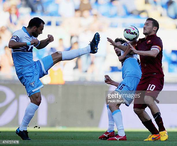 Francesco Totti of AS Roma competes for the ball with Santiago Gentiletti and Marco Parolo of SS Lazio during the Serie A match between SS Lazio and...