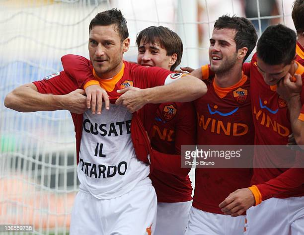 Francesco Totti of AS Roma displays the message 'scusate il ritardo' on his tshirt as he celebrates with his teammates after scoring a goal from the...
