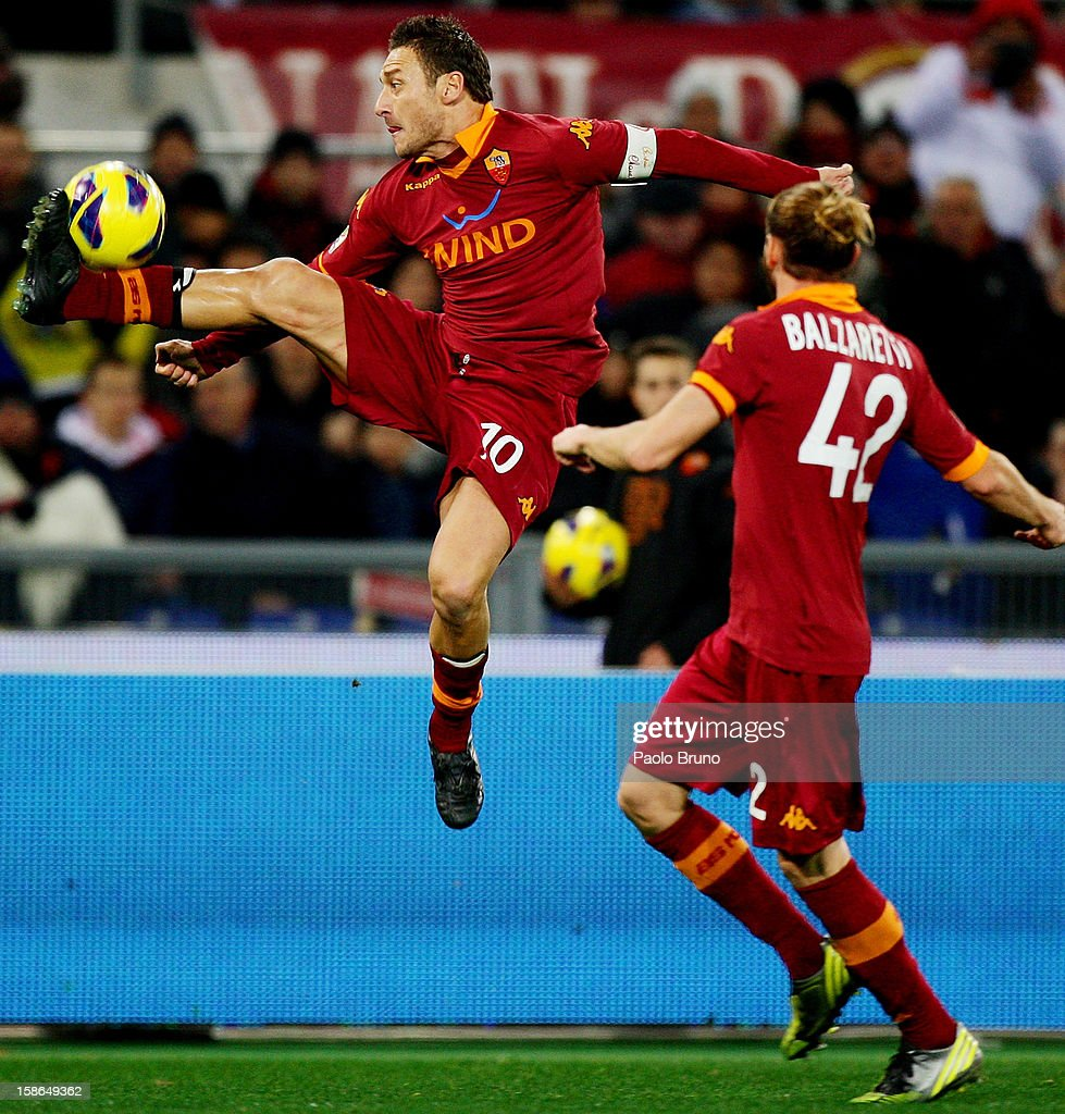 Francesco Totti (L) of AS Roma is airborne to control the ball as Federico Balzaretti watches him during the Serie A match between AS Roma and AC Milan at Stadio Olimpico on December 22, 2012 in Rome, Italy.