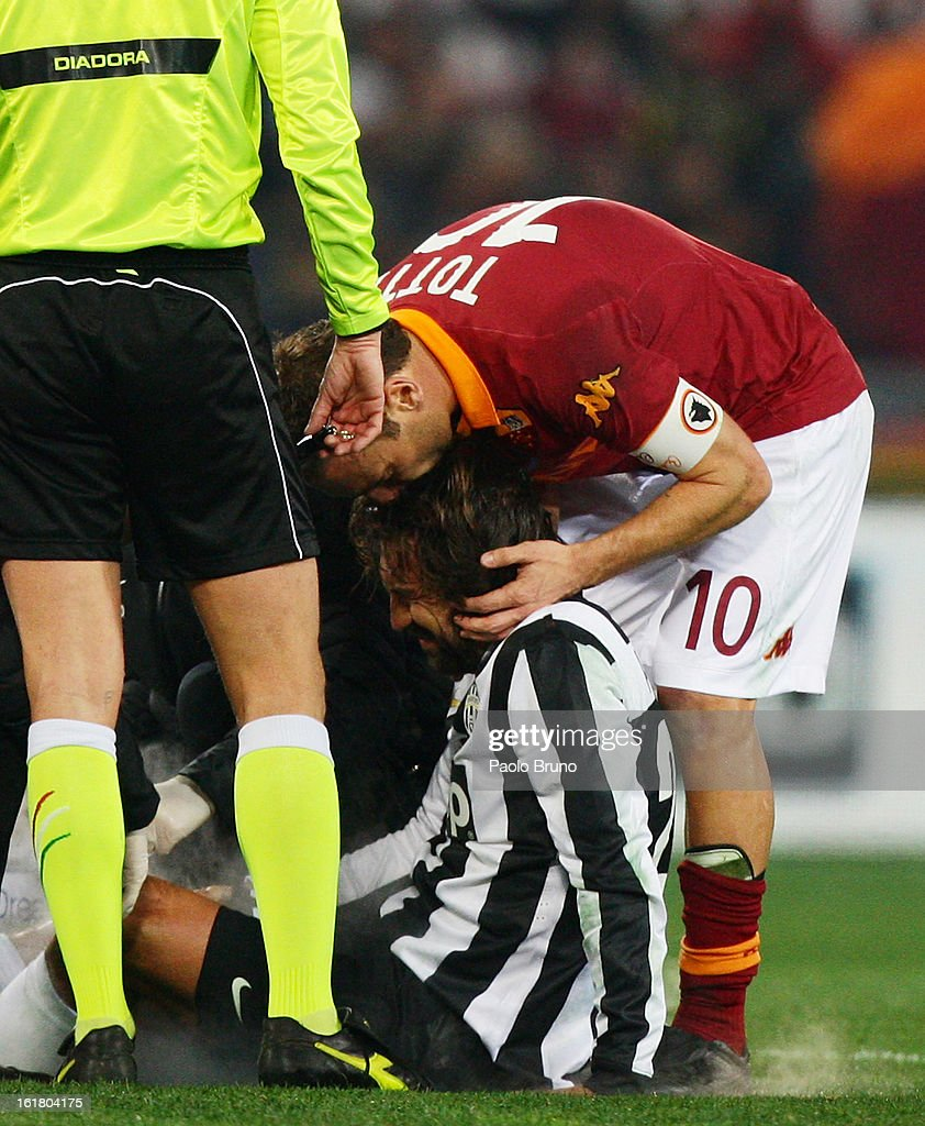 Francesco Totti (R) of AS Roma kisses an injured Andrea Pirlo of Juventus FC during the Serie A match between AS Roma and Juventus FC at Stadio Olimpico on February 16, 2013 in Rome, Italy.