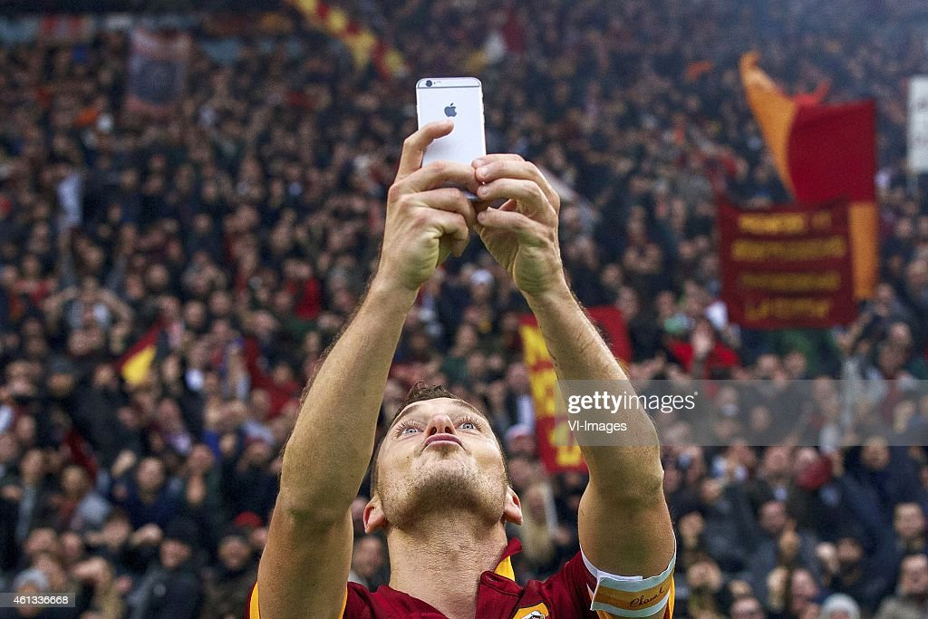 <a gi-track='captionPersonalityLinkClicked' href=/galleries/search?phrase=Francesco+Totti&family=editorial&specificpeople=208985 ng-click='$event.stopPropagation()'>Francesco Totti</a> of AS Roma selfie Apple iPhone during the Serie A match between AS Roma and Lazio Roma on January 11,2014 at the Stadio Olimpico in Rome, Italy.