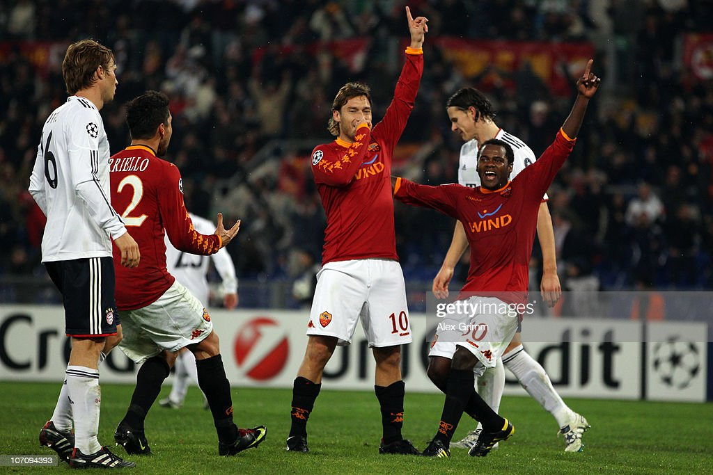 <a gi-track='captionPersonalityLinkClicked' href=/galleries/search?phrase=Francesco+Totti&family=editorial&specificpeople=208985 ng-click='$event.stopPropagation()'>Francesco Totti</a> (2R) of Roma celebrates his team's third goal with team mates <a gi-track='captionPersonalityLinkClicked' href=/galleries/search?phrase=Marco+Borriello&family=editorial&specificpeople=709800 ng-click='$event.stopPropagation()'>Marco Borriello</a> (2L) and <a gi-track='captionPersonalityLinkClicked' href=/galleries/search?phrase=Fabio+Simplicio&family=editorial&specificpeople=2104150 ng-click='$event.stopPropagation()'>Fabio Simplicio</a> (R) as <a gi-track='captionPersonalityLinkClicked' href=/galleries/search?phrase=Martin+Demichelis&family=editorial&specificpeople=240330 ng-click='$event.stopPropagation()'>Martin Demichelis</a> (L) of Muenchen reacts during the UEFA Champions League group E match between AS Roma and FC Bayern Muenchen at Stadio Olimpico on November 23, 2010 in Rome, Italy.