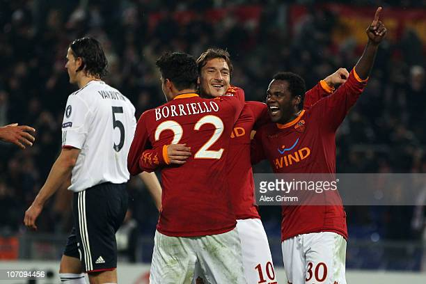 Francesco Totti of Roma celebrates his team's third goal with team mates Marco Borriello and Fabio Simplicio as Daniel van Buyten of Muenchen reacts...