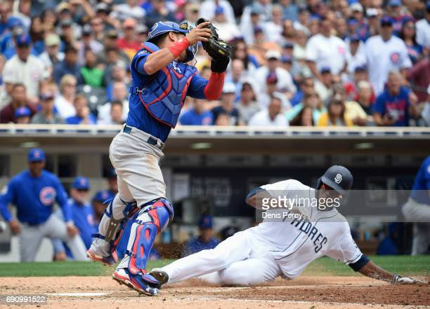 Franchy Cordero of the San Diego Padres scores ahead of the tag of Willson Contreras of the Chicago Cubs during the eighth inning of a baseball game...
