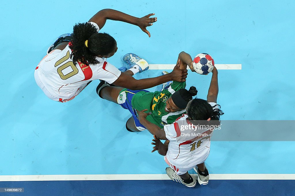 Francine Cararo#20 of Brazil shoots for goal under pressure from <a gi-track='captionPersonalityLinkClicked' href=/galleries/search?phrase=Isabel+Fernandes+-+Handball+Player&family=editorial&specificpeople=2956145 ng-click='$event.stopPropagation()'>Isabel Fernandes</a> #10 and <a gi-track='captionPersonalityLinkClicked' href=/galleries/search?phrase=Marcelina+Kiala&family=editorial&specificpeople=2130656 ng-click='$event.stopPropagation()'>Marcelina Kiala</a> #18 of Angola during the Women's Handball Preliminaries Group A match between Brazil and Angola on Day 9 of the London 2012 Olympic Games at the Copper Box on August 5, 2012 in London, England.