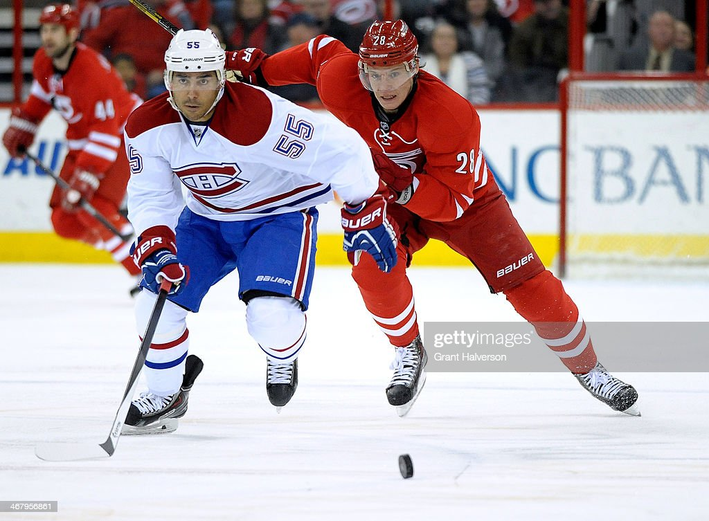 Francis Bouillon of the Montreal Canadiens and Alexander Semin of the Carolina Hurricanes chase a loose puck during a game at PNC Arena on February 8...