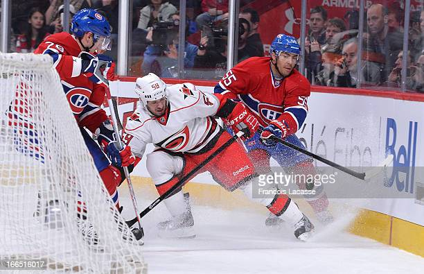 Francis Bouillon of the Montreal Canadiens and Chad LaRose of the Carolina Hurricanes battle for the puck during the NHL game on April 1 2013 at the...