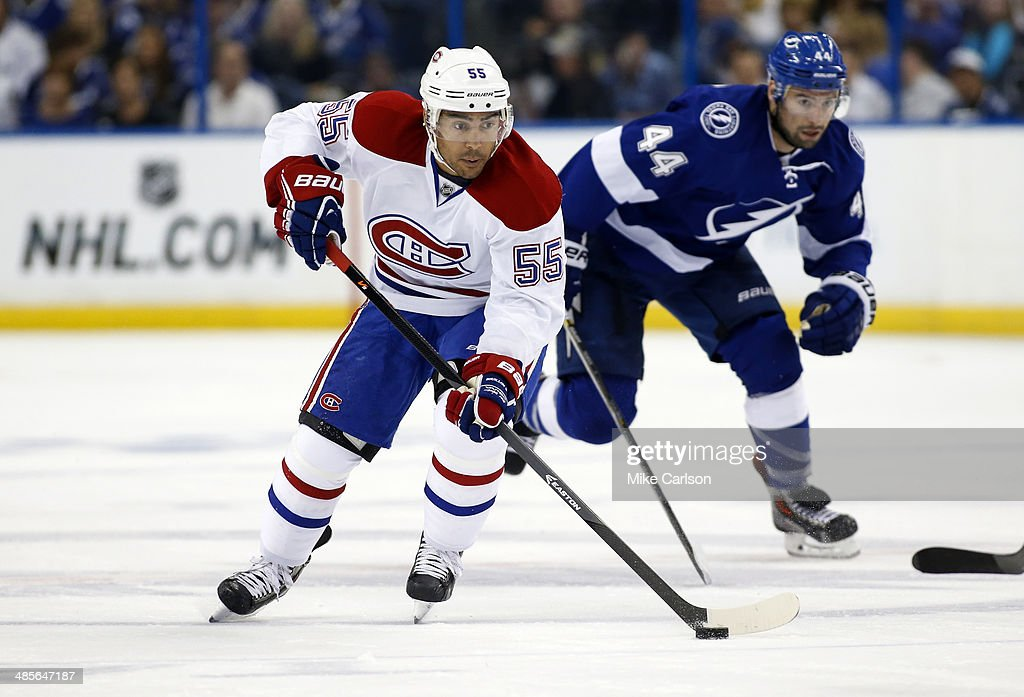 Francis Bouillon of the Montreal Canadiens brings the puck up the ice past Nate Thompson of the Tampa Bay Lightning in Game One of the First Round of...