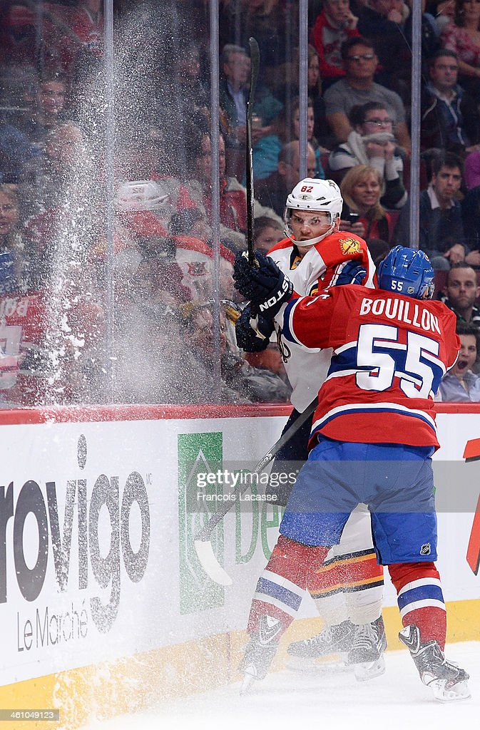 Francis Bouillon of the Montreal Canadiens checks into the boards Tomas Kopecky of the Florida Panthers during the NHL game on January 6 2014 at the...