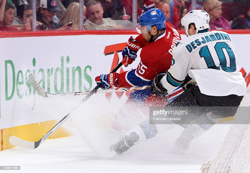<a gi-track='captionPersonalityLinkClicked' href=/galleries/search?phrase=Francis+Bouillon&family=editorial&specificpeople=215165 ng-click='$event.stopPropagation()'>Francis Bouillon</a> #55 of the Montreal Canadiens fights for the puck against <a gi-track='captionPersonalityLinkClicked' href=/galleries/search?phrase=Andrew+Desjardins&family=editorial&specificpeople=2748431 ng-click='$event.stopPropagation()'>Andrew Desjardins</a> #10 of the San Jose Sharks during the NHL game on October 26, 2013 at the Bell Centre in Montreal, Quebec, Canada.