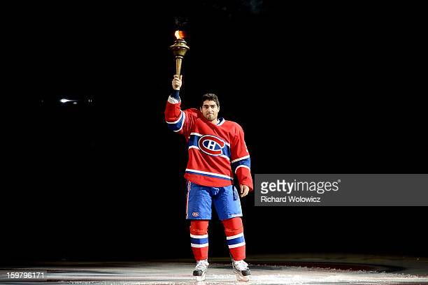 Francis Bouillon of the Montreal Canadiens of the Montreal Canadiens raises a torch during pregame ceremonies prior to facing the Toronto Maple Leafs...