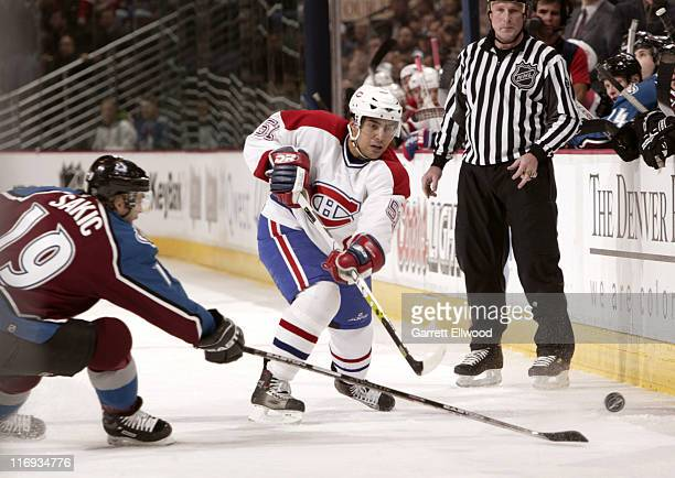 Francis Bouillon of the Montreal Canadiens sends the puck past Joe Sakic of the Colorado Avalanche during the game on January 11 2006 at Pepsi Center...