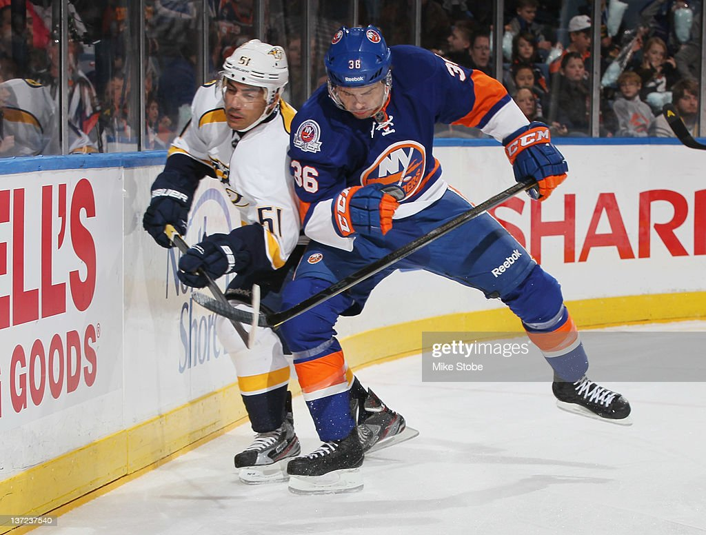 Francis Bouillon of the Nashville Predators is checked by Tim Wallace of the New York Islanders at Nassau Veterans Memorial Coliseum on January 16...