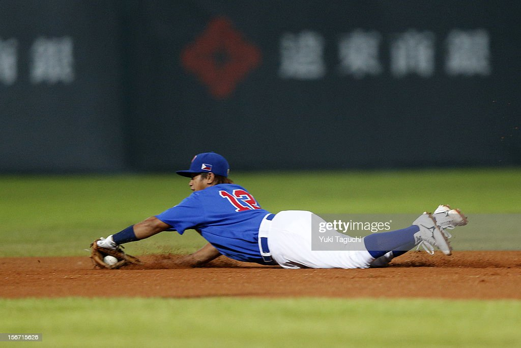 Francis Candela #12 of Team Philippines makes a backhanded diving play in the top of the sixth inning during Game 5 of the 2013 World Baseball Classic Qualifier against Team New Zealand at Xinzhuang Stadium in New Taipei City, Taiwan on Saturday, November 17, 2012.