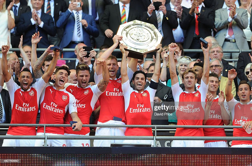 Francis Coquelin, Hector Bellerin, Olivier Giroud, Per Mertesacker, Mikel Arteta and Nacho Monreal of Arsenal lift the Community Shield after the FA Community Shield match between Chelsea and Arsenal at Wembley Stadium on August 2, 2015 in London, England.