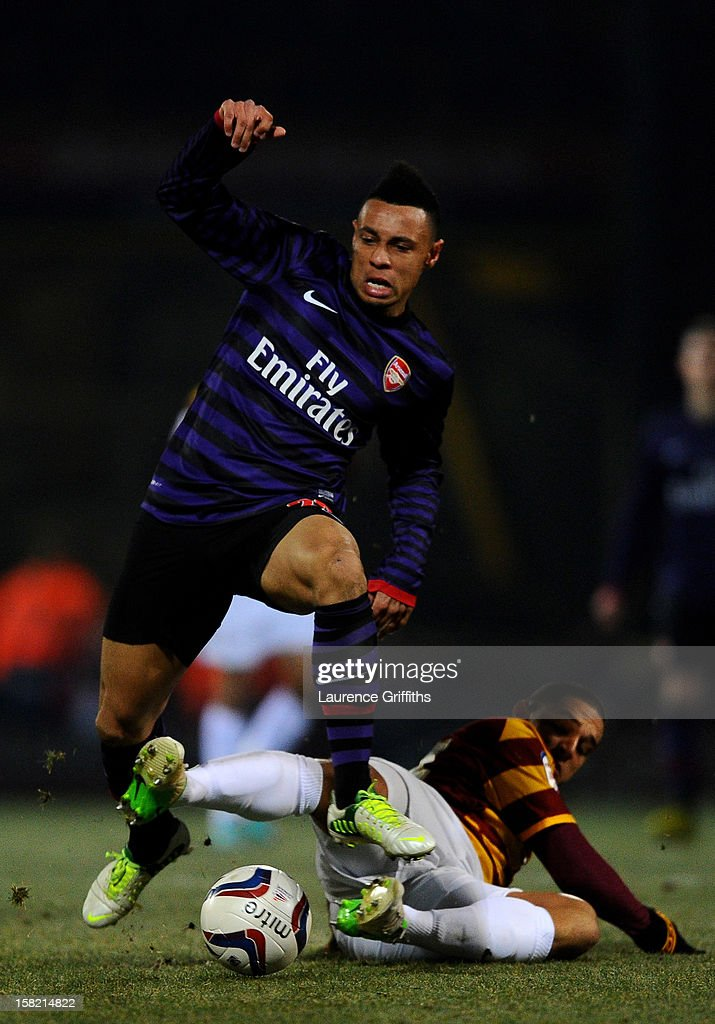 Francis Coquelin of Arsenal hurdles the tackle from Nathan Doyle of Bradford during the Capital One Cup quarter final match between Bradford City and Arsenal at the Coral Windows Stadium, Valley Parade on December 11, 2012 in Bradford, England.
