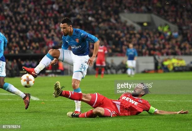 Francis Coquelin of Arsenal is challenged by Dominic Maroh of Cologne during the UEFA Europa League group H match between 1 FC Koeln and Arsenal FC...