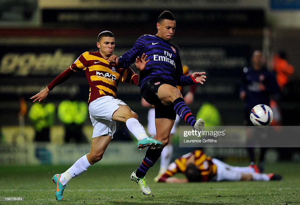 Francis Coquelin of Arsenal is challenged by Nahki Wells of Bradford during the Capital One Cup quarter final match between Bradford City and Arsenal at the Coral Windows Stadium, Valley Parade on December 11, 2012 in Bradford, England.
