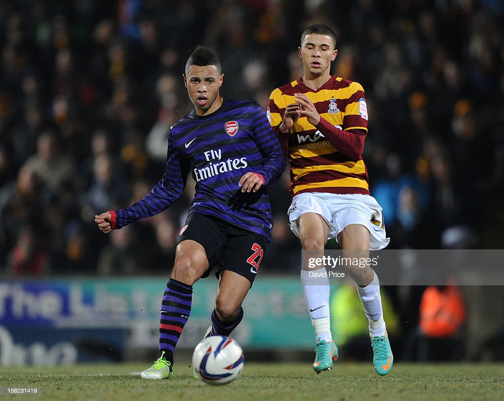 Francis Coquelin of Arsenal is challenged by Nahki Wells of Bradford during the Capital One Cup match between Arsenal and Bradford City at Coral Windows Stadium, Valley Parade on December 11, 2012 in Bradford, England.