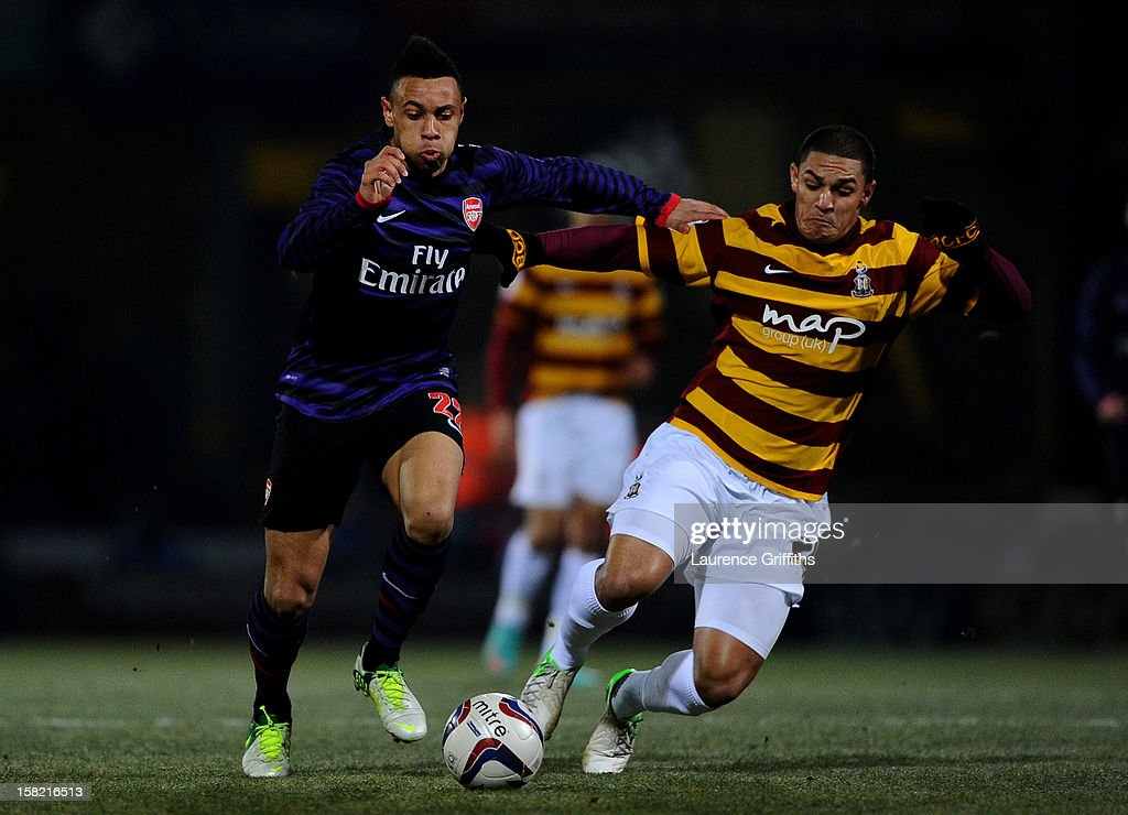 Francis Coquelin of Arsenal is challenged by Nathan Doyle of Bradford during the Capital One Cup quarter final match between Bradford City and Arsenal at the Coral Windows Stadium, Valley Parade on December 11, 2012 in Bradford, England.