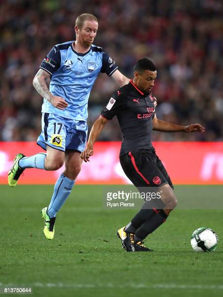 Francis Coquelin of Arsenal is tacked by David Carney of Sydney FC during the match between Sydney FC and Arsenal FC at ANZ Stadium on July 13 2017...