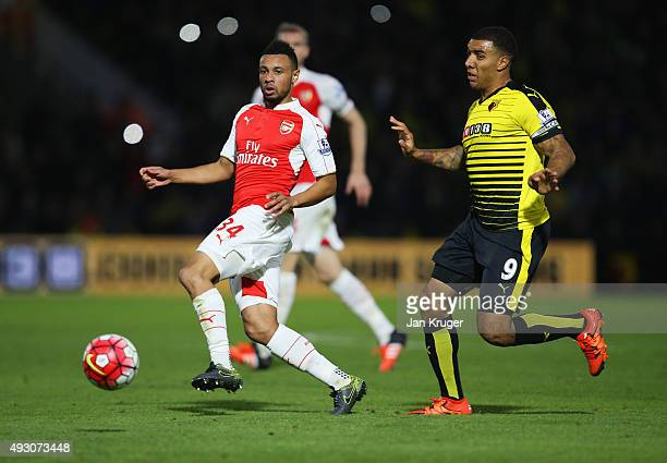 Francis Coquelin of Arsenal moves the ball away from Troy Deeney of Watford during the Barclays Premier League match between Watford and Arsenal at...