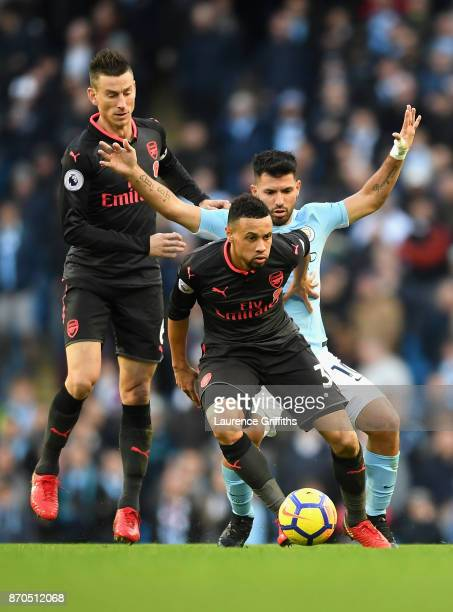 Francis Coquelin of Arsneal and Sergio Aguero of Manchester City battle for possession during the Premier League match between Manchester City and...
