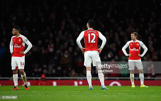 Francis Coquelin Olivier Giroud and Nacho Monreal of Arsenal stand dejected after Wayne Routledge of Swansea City scored the equalising goal during...
