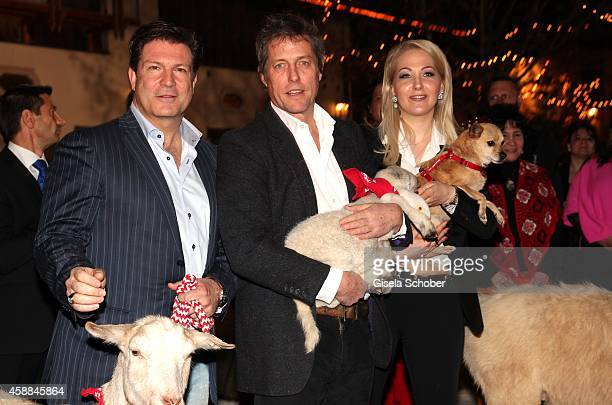 Francis Fulton Smith Hugh Grant with lamb and Kathrin Glock during the Opening of the Gut Aiderbichl Christmas Market on November 11 2014 in Henndorf...
