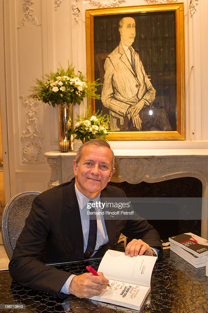 Francis Huster poses as he signs a copy of his book 'And Dior Created Woman' during a signing at Dior Boutique on November 19, 2012 in Paris, France.