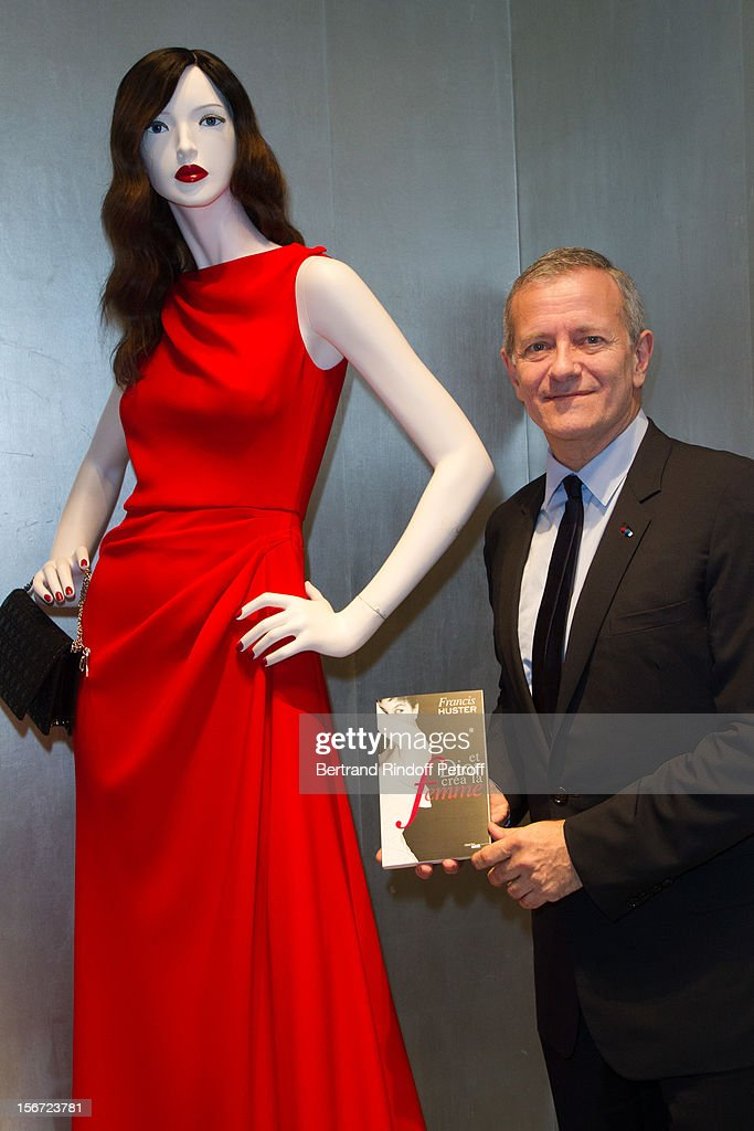 Francis Huster poses with a copy of his book 'And Dior Created Woman' during a signing at Dior Boutique on November 19, 2012 in Paris, France.