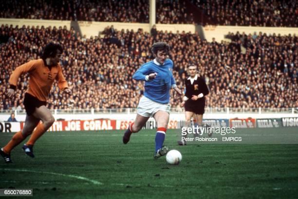 Francis Munro of Wolverhampton Wanderers tracks Rodney Marsh of Manchester City