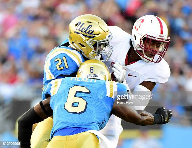 Francis Owusu of the Stanford Cardinal fumbles after a hit from Tahaan Goodman and Adarius Pickett of the UCLA Bruins during the second quarter at...