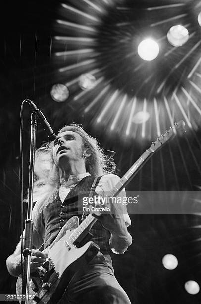 Francis Rossi singer and guitarist with Status Quo singing into a microphone while playing the guitar during a live concert performance by the band...