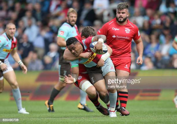 Francis Sali of Harlequins is tackled by Jerry Sexton of Jersey Red during the pre season match between Harlequins and Jersey Red at the Twickenham...