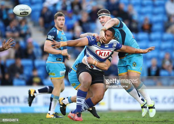 Francis Tualau of the Bulldogs offloads the ball during the round 25 NRL match between the Gold Coast Titans and the Canterbury Bulldogs at Cbus...