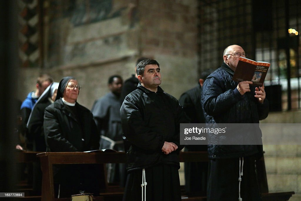 Franciscan friars pray during a mass at the Basilica of St. Francis of Assisi which holds the tomb of Saint Francis of Assisi on March 15, 2013 in Assisi, Italy. Cardinal Jorge Mario Bergoglio took the name Pope Francis after Saint Francis of Assisi who had renounced a life of privilege, by giving away all his possessions, wearing coarse woolen clothes and living in a humble hut after he took a vow of poverty.